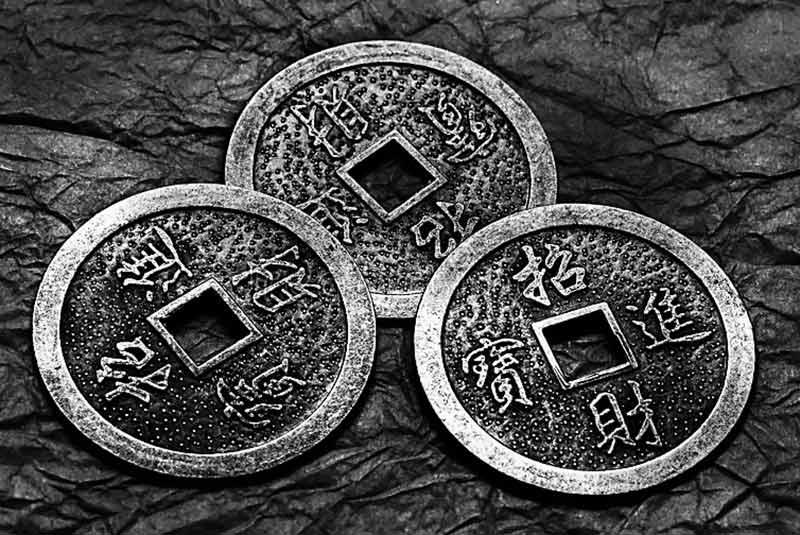 Le monete con cui si consulta l'I Ching. La moneta cinese tradizionale ha un foro quadrato al centro che rappresenta la terra, mentre la loro forma circolare rappresenta il cielo. In realtà all'origine del foro vi è un motivo pratico: le monete venivano legate alla cintura con un laccio, in modo da essere facilmente trasportabili.