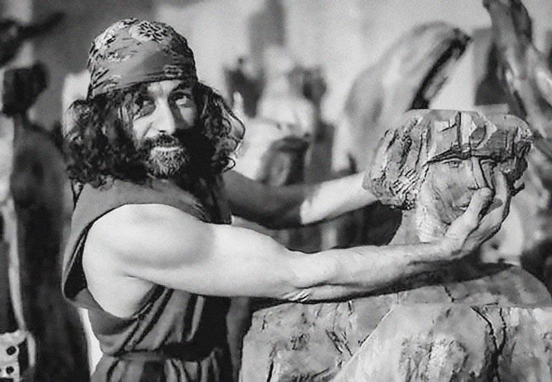 Mauro Corona intento a dimostrare il modo migliore di uccidere in maniera indolore una scultura lignea.